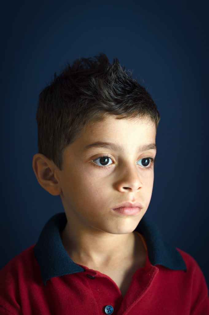 portrait photo of boy wearing red and black polo shirt